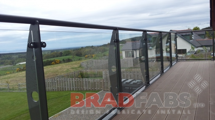 Large modern balcony in mild steel, galvanised and powder coated, with support legs and spiral staircase at the end. with glass infill panels on the balcony and vertical bar balustrade and durbar treads on the spiral staircase. By Bradfabs