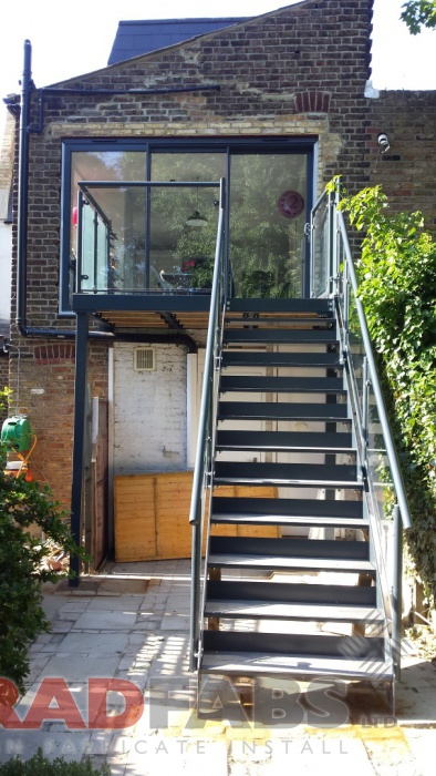 small balcony with a support leg, and additional straight staircase leading to the garden. Manufactured in mild steel, galvanised and powder coated with glass infill panels and open treads on the stairs by Bradfabs