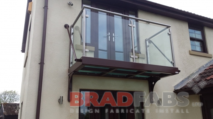Balcony manufactured in mild steel, galvanised and powder coated with glass infill panels and stainless steel handrail with glass floor by Bradfabs
