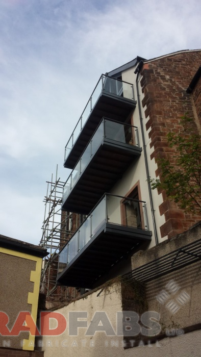 Balconies for buildng of apartments. Manufactured in mild steel, galvanised and powder coated with glass infill panels and composite decked flooring by Bradfabs
