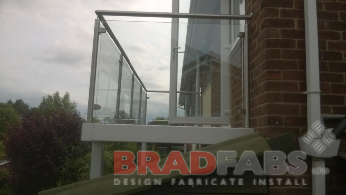 Large balcony with legs, manufactured in mild steel, galvanised and powder coated white, with stainless steel balustrade, glass infill panels and complete with composite decked flooring by Bradfabs