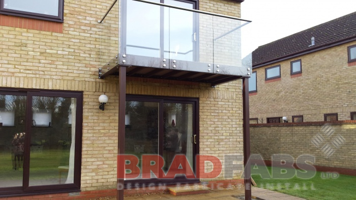 Balcony with legs, with front fixed glass balustrade and stainless steel handrail, in mild steel, galvanised and powder coated by Bradfabs