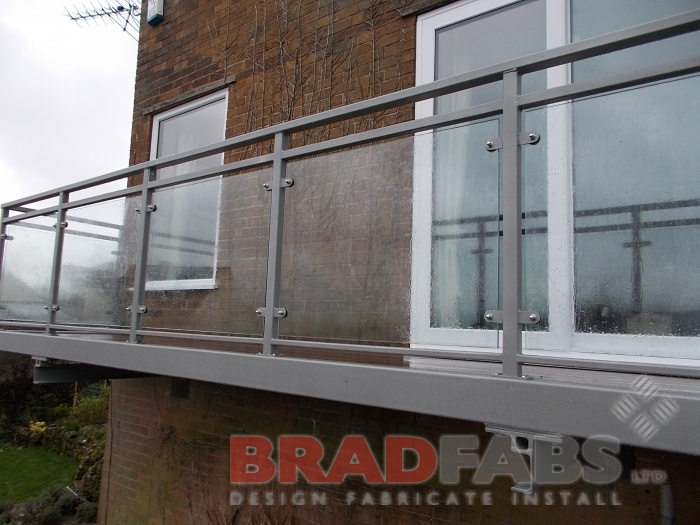 Long balcony going along the length of the house,  manufactured in mild steel, galvanised and powder coated frame with glass infill panels and composite decked flooring by Bradfabs