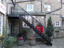 Access staircase to first floor shop within a courtyard area.
