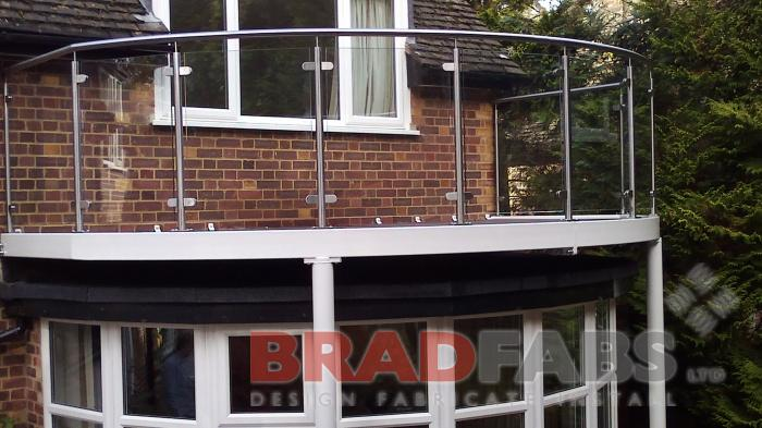 Large curved balcony with legs, manufactured in mild steel, galvanised and powder coated white with glass infill panels and stainless steel balustrade. Complete with composite decked flooring by Bradfabs
