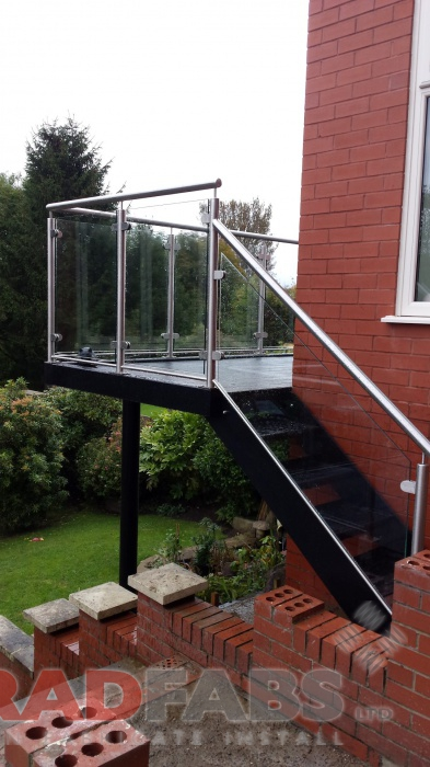 Straight staircase at the end of a large balcony, with durbar treads and glass infill panels, with stainless steel handrail by Bradfabs