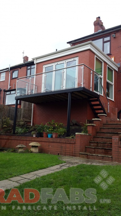 Large balcony with legs at a domestic property, with a straight staircase at the end. Manufactured in mild steel, galvanised and powder coated, with glass infill panels and stainless steel balustrade by Bradfabs