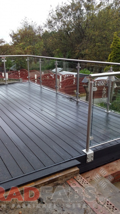 large balcony with composite decked flooring, stainless steel balustrade and glass infill panels by Bradfabs