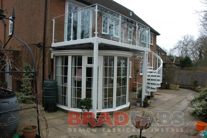 Modern balcony over a conservatory with a spiral staircase at the end. Manufactured in mild steel, galvanised and powder coated white, with glass infill panels on balcony and vertical bar balustrade on the spiral. The spiral also has durbar treads.