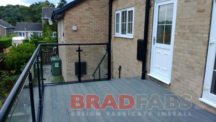 Long balcony with small straight staircase at the end, with four support legs, manufactured in mild steel, galvanised and powder coated black with glass infill panels and composite decked flooring, and durbar treads by Bradfabs