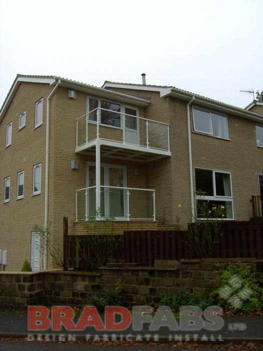 Two balconies on this customers house - a very attractive and unique design. One balcony to upstairs door and one balcony from patio doors downstairs, both manufactured in mild steel, galvanised and powder coated white with glass infill panels by Bradfabs