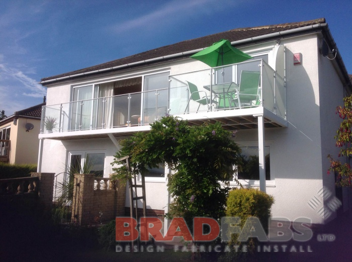 Mild steel, galvanised and powder coated in white balcony with glass infill panels, complete with composite decked flooring by Bradfabs