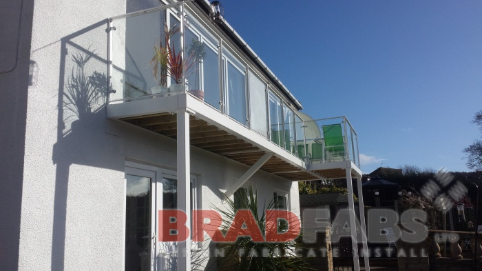 Mild steel, galvanised and powder coated in white balcony with legs, with glass infill panels, complete with composite decked flooring by Bradfabs
