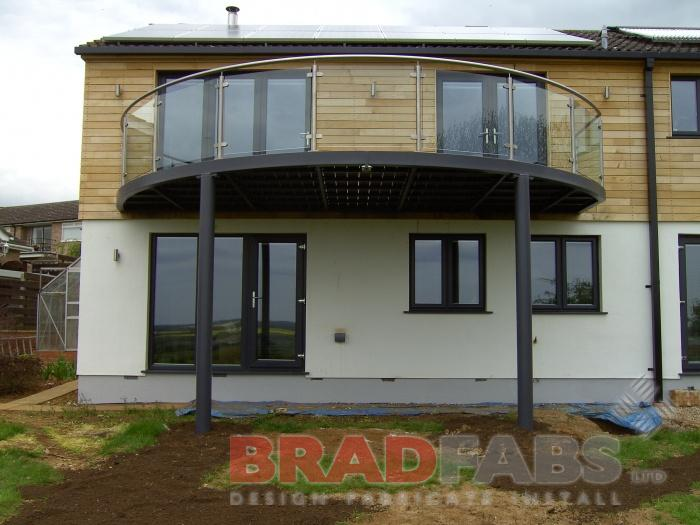 mild steel galvanised and powder coated large circular balcony with glass infill panels and stainless steel handrail by bradfabs