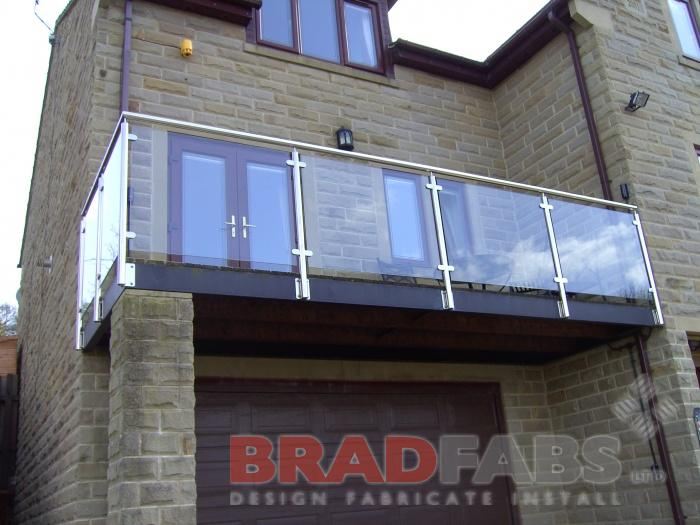 After image, modern balcony with stainless steel balustrade and glass infill panels, complete with composite decked flooring by Bradfabs
