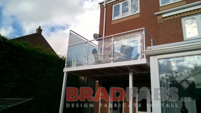 Balcony with two support legs and frosted glass to one side to allow for customers privacy, mild steel, galvanised and powder coated white frame and legs and glass infill panels at the front by Bradfabs