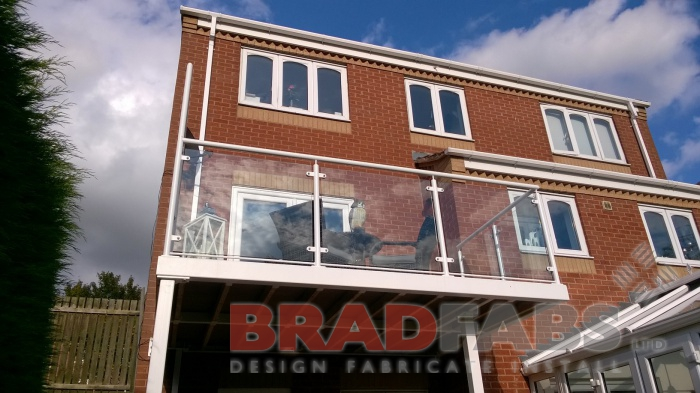 This photo shows looking up at the customers new balcony, with two support legs, manufactured in mild steel, galvanised and powder coated white by Bradfabs