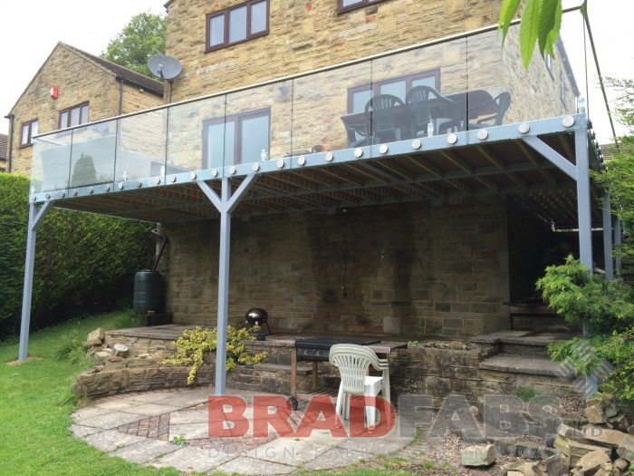 Extra large balcony with legs manufactured in mild steel, galvanised and powder coated with glass balustrade and stainles steel handrail, complete with composite decked floor by Bradfabs