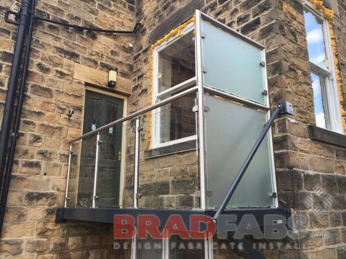 Balcony in mild steel, galvanised and powder coated frame with glass infill panels and stainless steel handrail, privacy glass to one side and complete with composite decked flooring by Bradfabs