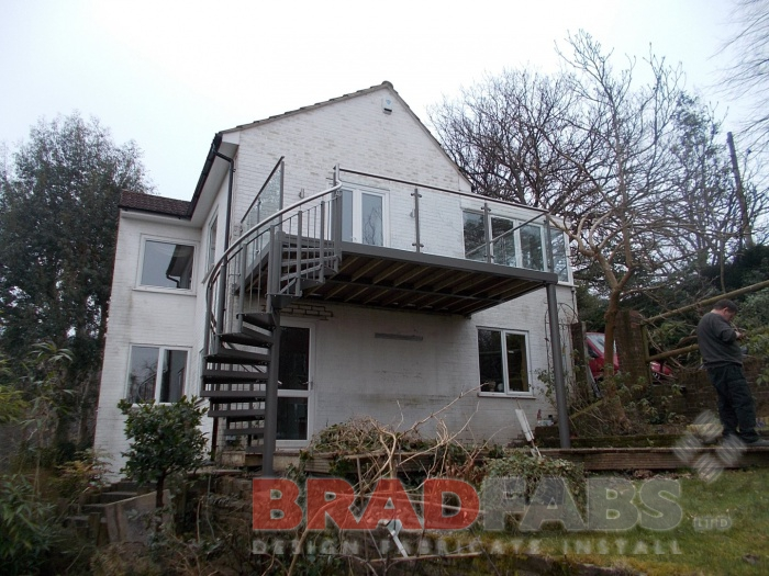 Large stunning balcony with added spiral staircase at the end to make for attractive access to the customers garden, in mild steel, galvanised and powder coated gray, with glass infill panels on the balcony, vertical bar balustrade on the spiral staircase, durbar treads on the staircase and composite decked flooring on the balcony. All by Bradfabs