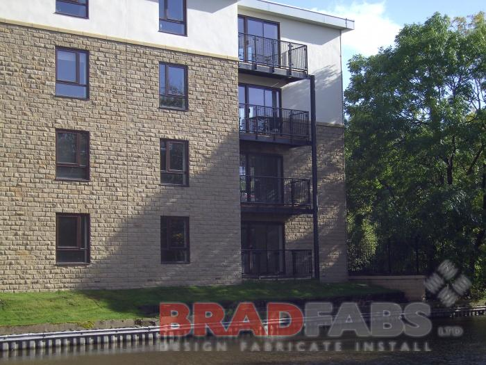 Balconies on a small modern block of flats, manufactured in mild steel, galvanised and powder coated black with vertical bar balustrade and composite decked flooring by Bradfabs