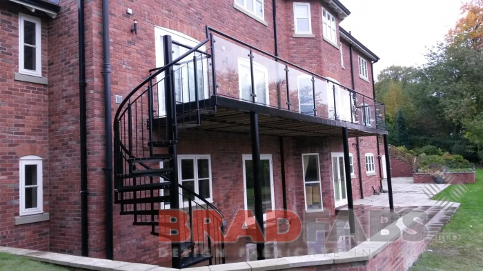 Large modern balcony manufactured in mild steel, galvanised and powder coated black, with glass infill panels and spiral staircase at the end, with vertical bar balustrade and durbar treads by Bradfabs