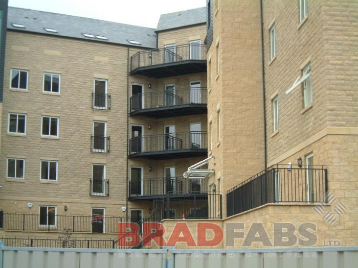 A view of four balconies designed, supplied and installed by Bradfabs, and the new railings surrounding new flats, in mild steel, galvanised and powder coated black with vertical bar balustrade on all by Bradfabs