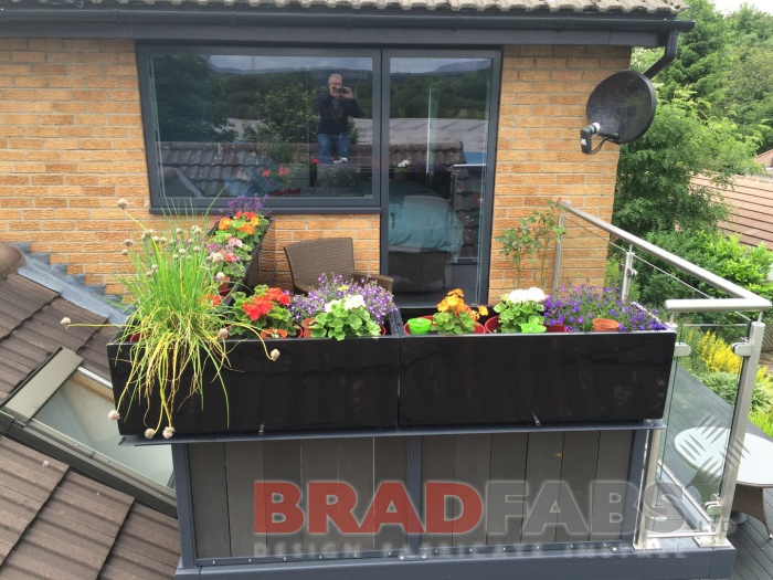 Beauitful balcony with two support legs, manufactured in mild steel, galvanised and powder coated with glass infill panels and stainless steel balustrade by Bradfabs