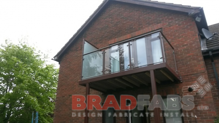 Small balcony with two support legs and privacy screen at one side, manufactured in mild steel, galvanised and powder coated brown with glass infill panels and complete with composite decked flooring by Bradfabs