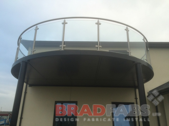 Beautiful large curved modern balcony with legs. Manufactured in mild steel, galvanised and powder coated, glass infill panels and stainless steel balustrade complete with composite decked flooring by Bradfabs