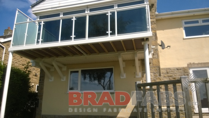 Large balcony with two support legs and privacy screen to one side manufactured in mild steel, galvanised and powder coated white, with glass infill panels complete with composite decked flooring by Bradfabs