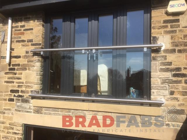 Modern Juliette balcony by Bradfabs with glass balustrade and stainless steel top and bottom rail.