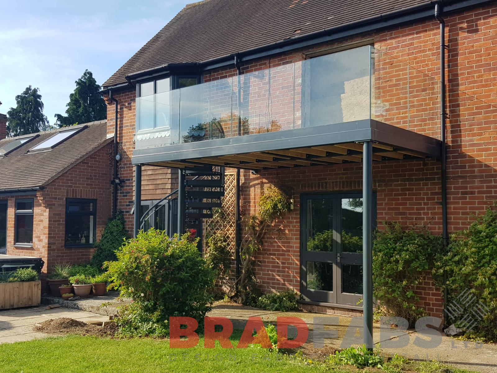 Metal and infinity glass balcony with steel spiral installed by UK Manufacturers Bradfabs
