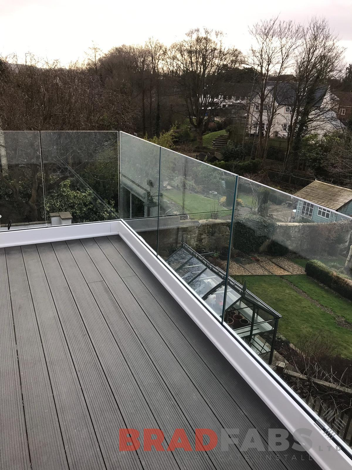 Stunning balcony with infinity glass balustrade and composite decked flooring, in mild steel, galvanised and powder coated by Bradfabs