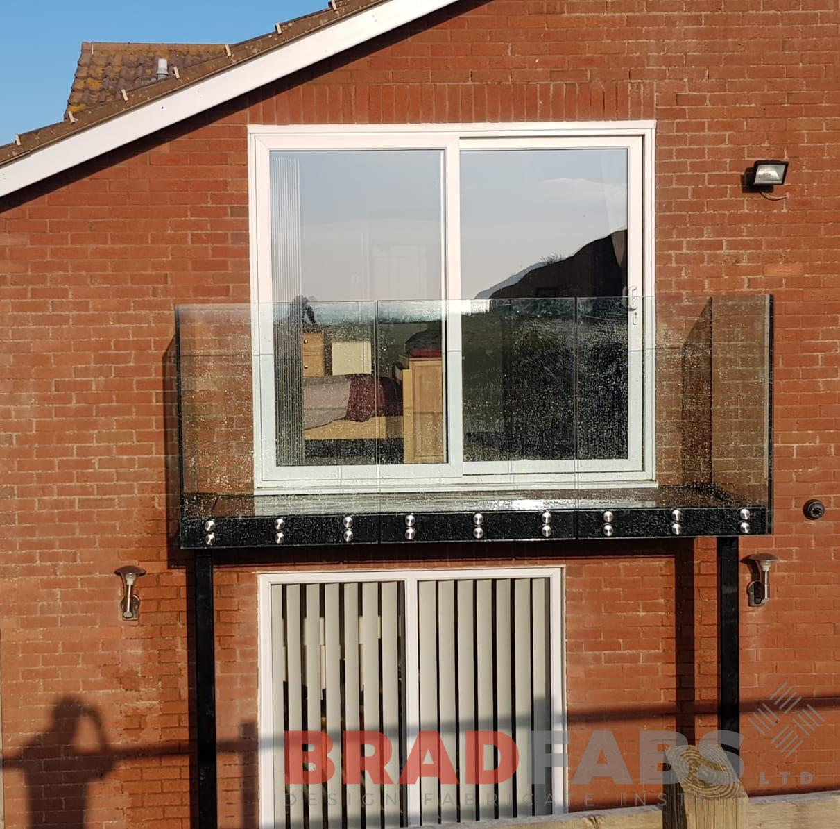 Beautiful baclony with two support legs and very popular front face fixed infinity glass balustrade by Bradfabs