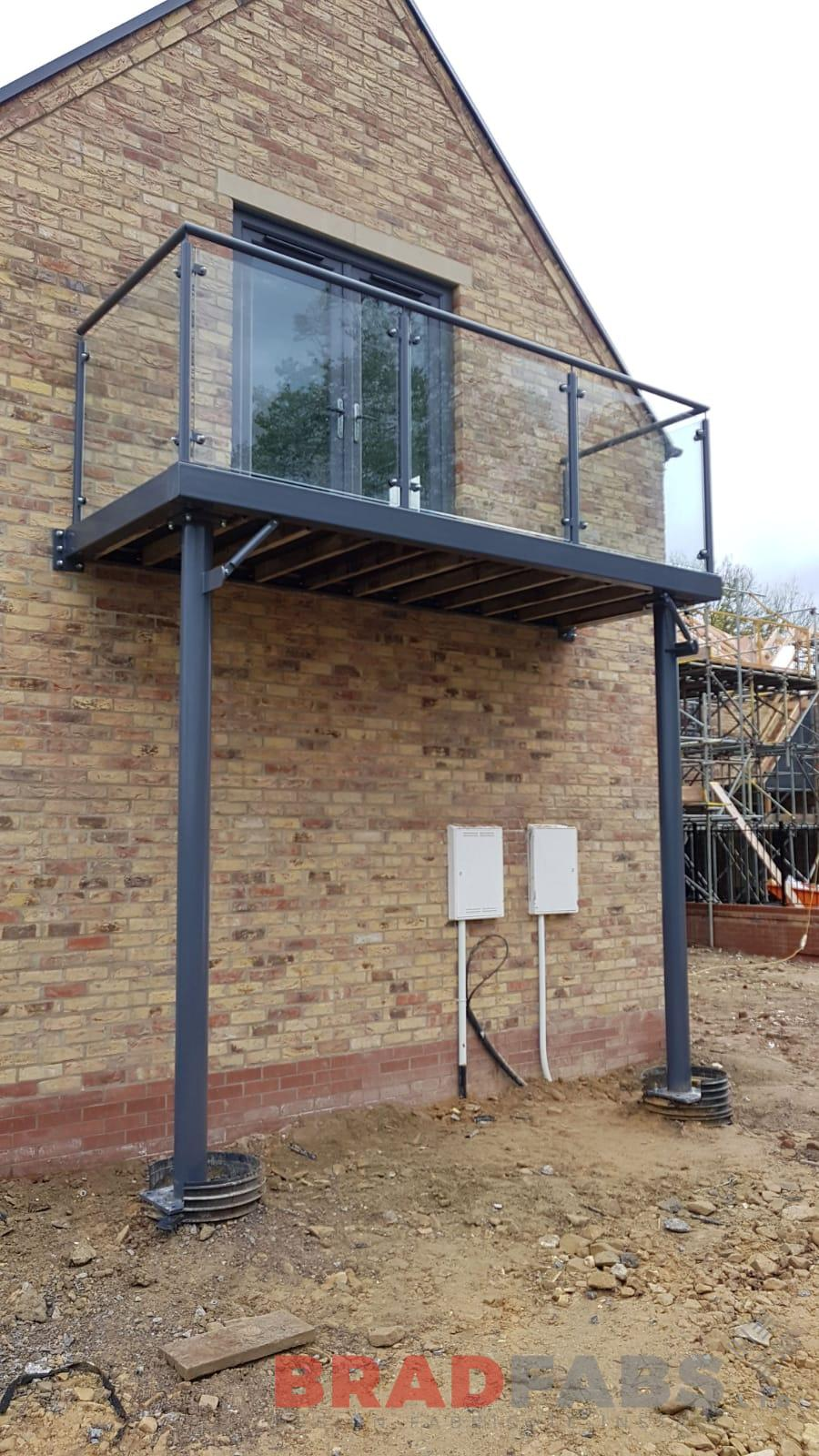 Bespoke balcony manufactured in mild steel, galvanised and powder coated grey, with two support legs, glass infill panels and composite decked flooring by Bradfabs