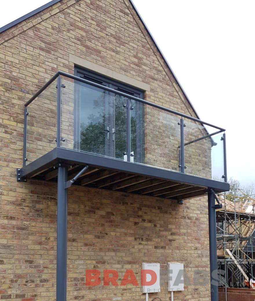 Bespoke design by Bradfabs, mild steel balcony, galvanised, powder coated with glass infill panels and composite decked flooring