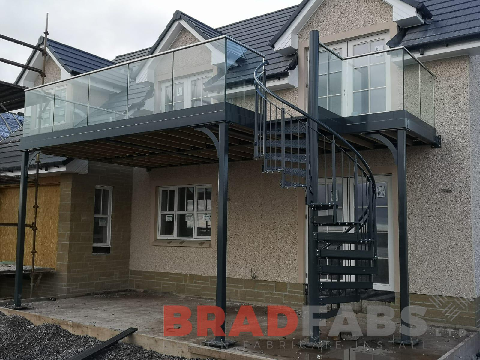 large balcony with three support legs, manufactured in mild steel, galvanised and powder coated with spiral staircase at the end, infinity glass balustrade and stainless steel handrail on the balcony and vertical bar balustrade on the spiral by Bradfabs