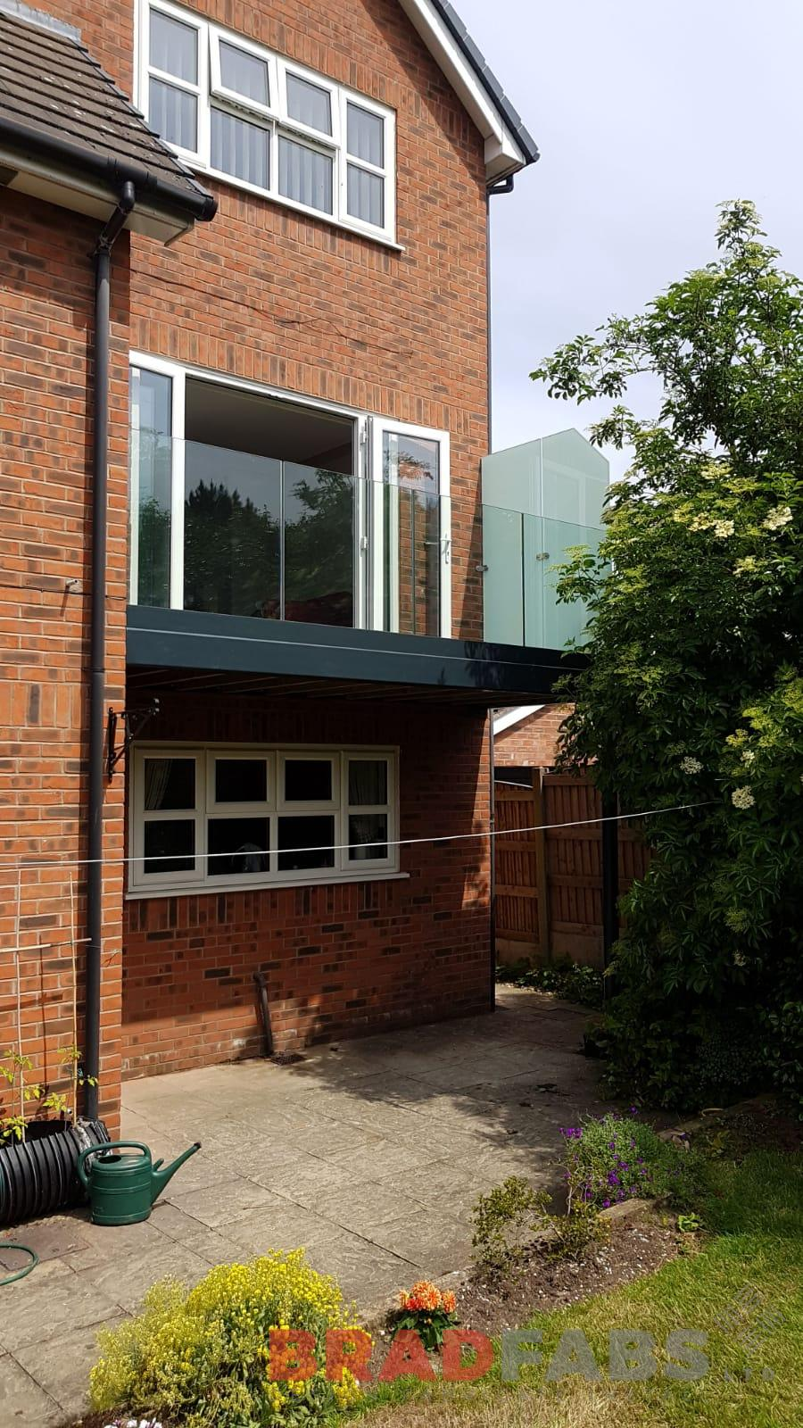 Beautiful modern home addition, a mild steel, galvanised and powder coated balcony with supporting legs and privacy glass to one side complete with composite decked flooring by Bradfabs