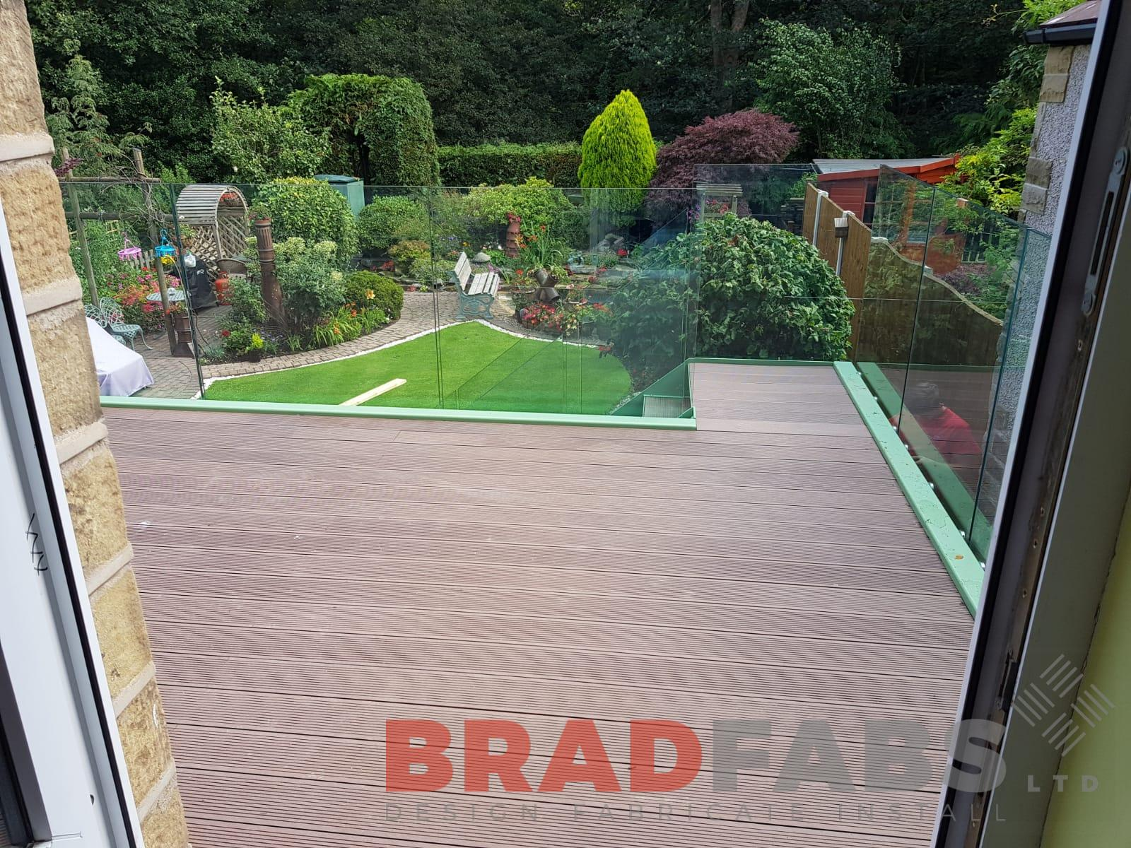 mild steel galvanised and powder coated balcony frame with bolt on infinity glass balustrade and complete with composite decked flooring by Bradfabs
