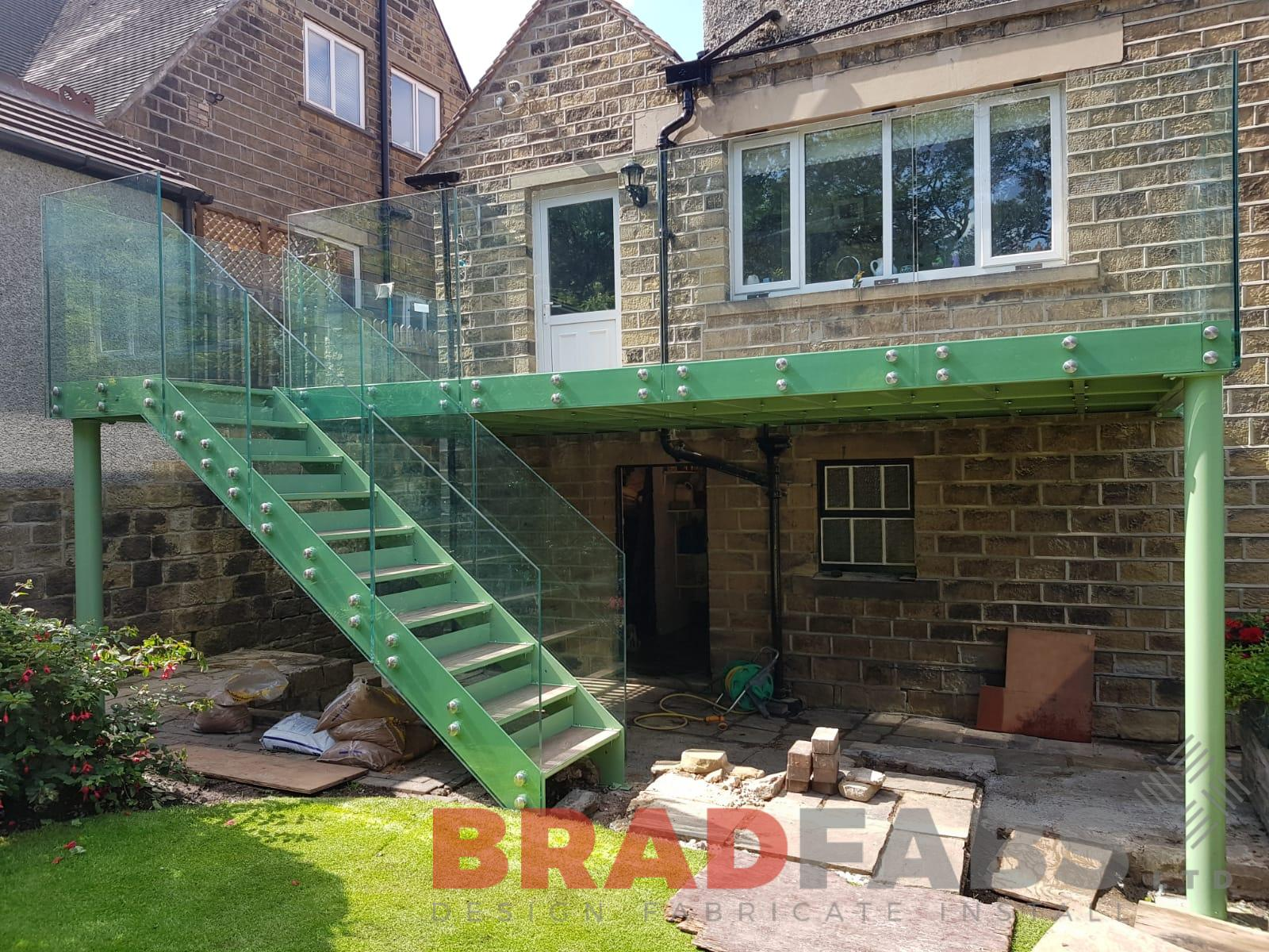 Mild steel, galvanised and powder coated balcony with bolt on infinity glass balustrade and straight staircase by Bradfabs