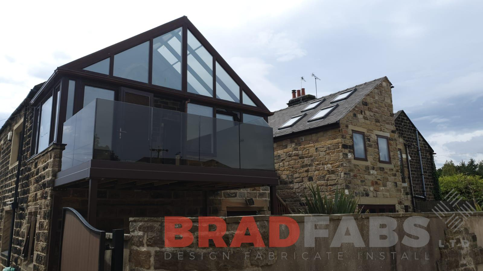 Balcony with supporting legs and bronze tinted laminated infinity glass balustrade with privacy screen to one side by Bradfabs