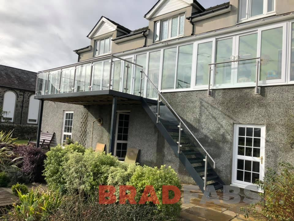 Bespoke balcony with staircase by Bradfabs Ltd, stainless steel and glass balustrade, composite decked flooring, durbar treads, mild steel and galvanised, powder coated