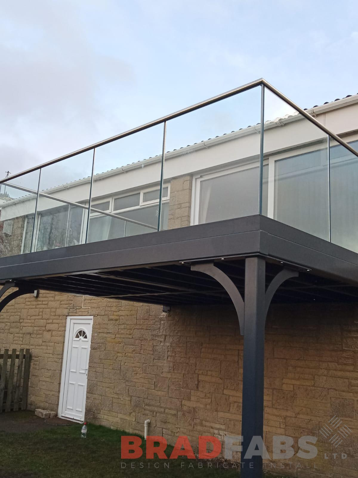 large steel balcony with infinity glass balustrade and stainless steel top rail by Bradfabs