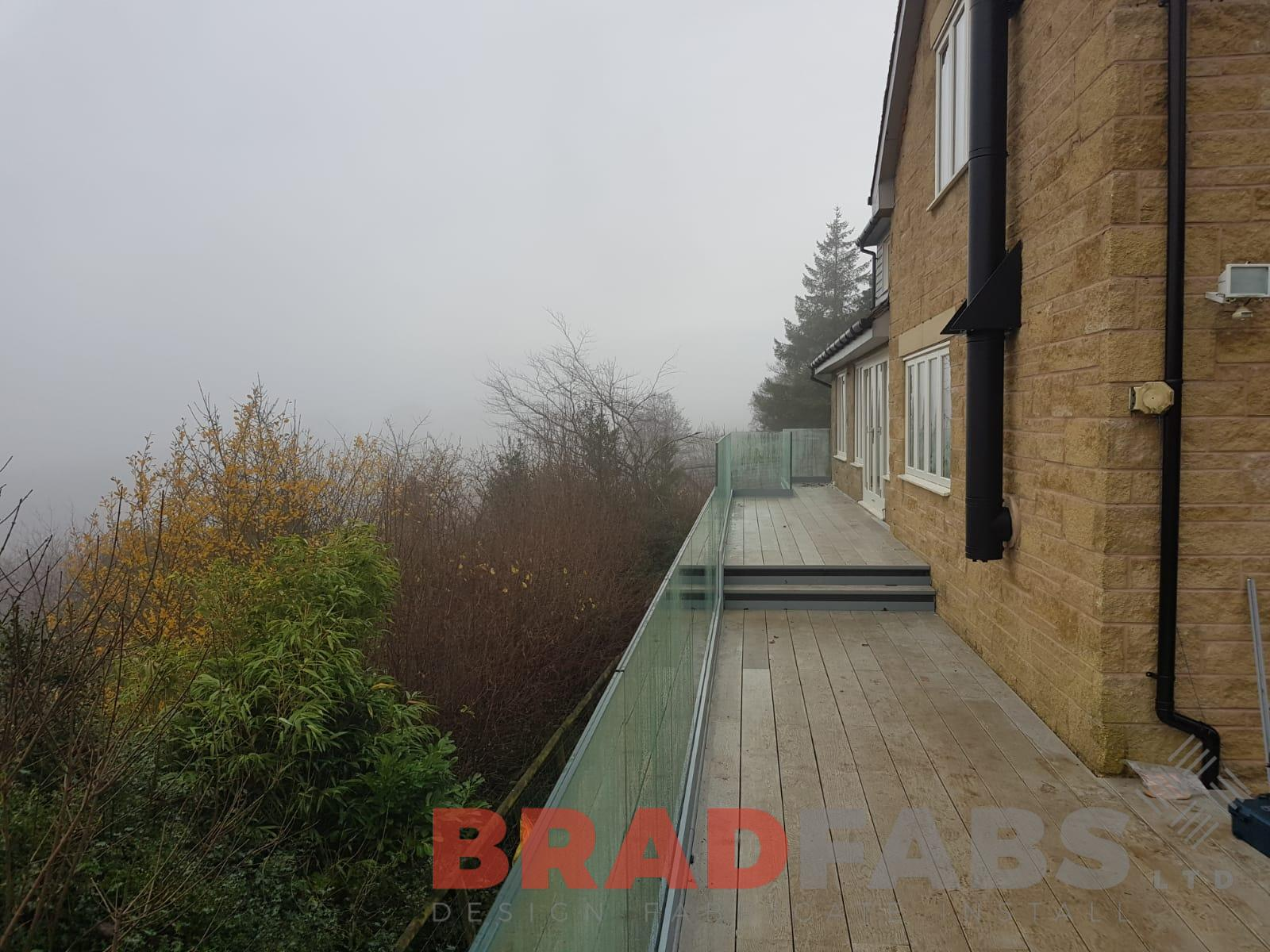 Beautiful modern balcony with infinity galss balustrade and milboard decking by Bradfabs UK LTD