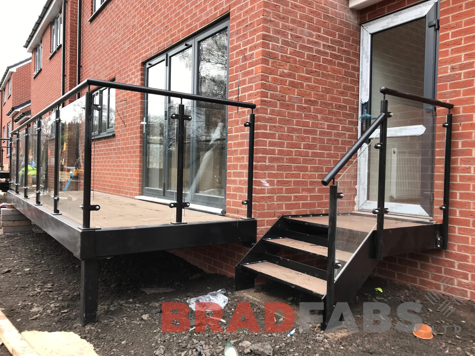 Mild steel balustrade, galvanised and powder coated black, with glass infill panels, external for commercial property by Bradfabs.