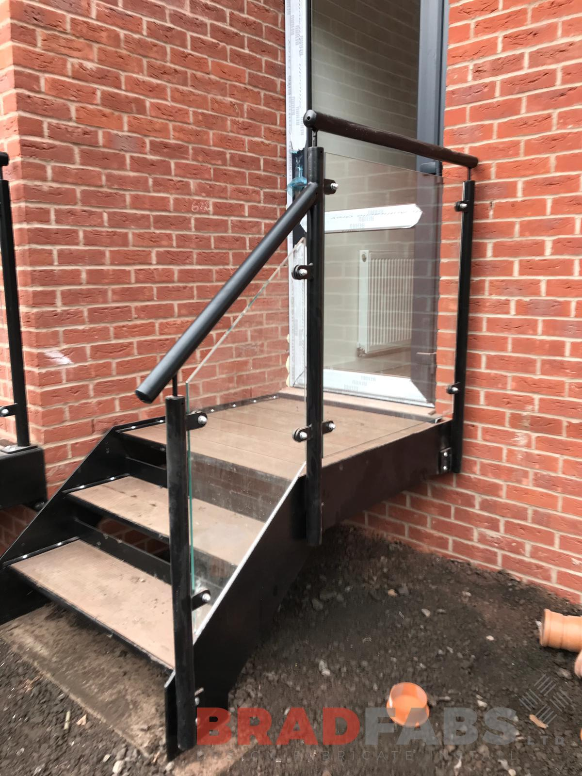 Small stairs with open treads in mild steel, galvanised and powder coated black, with glass infill panels, by Bradfabs