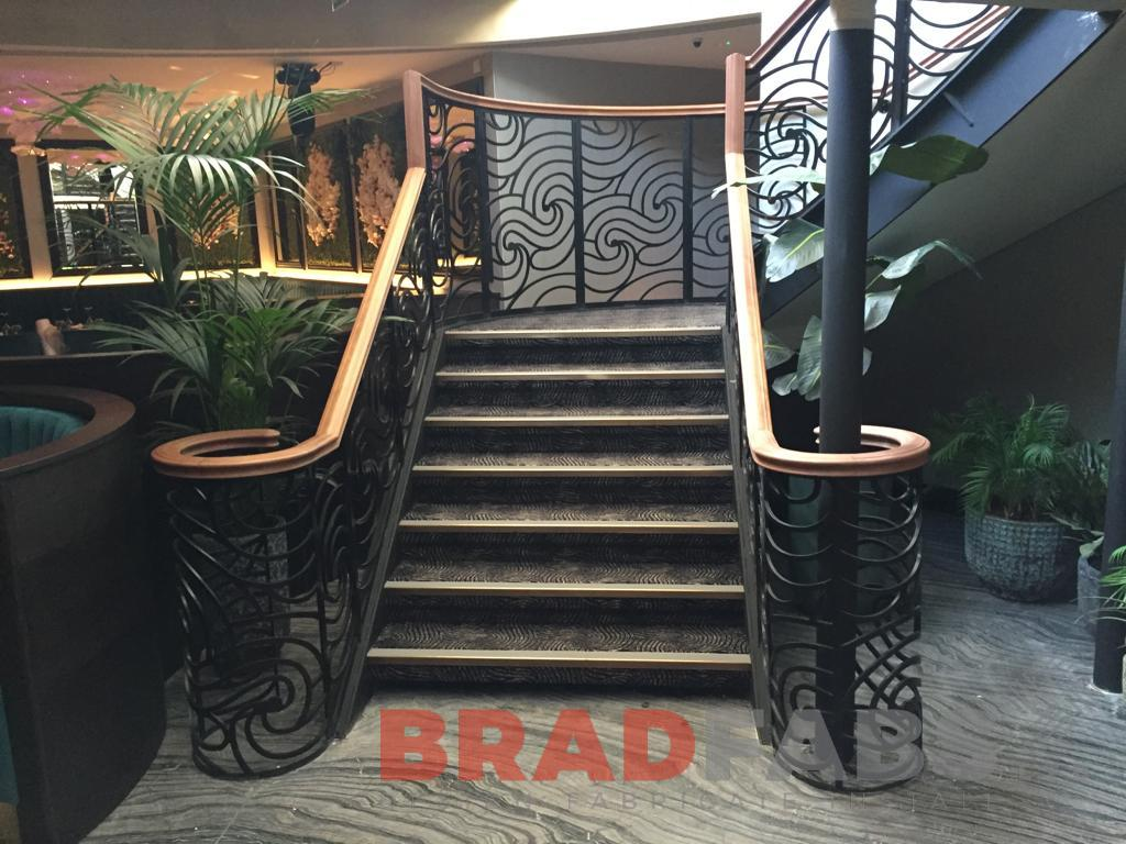 The bottom of the new large staircase by Bradfabs, manufactured in mild steel and powder coated with decorative balustrade and timber handrails