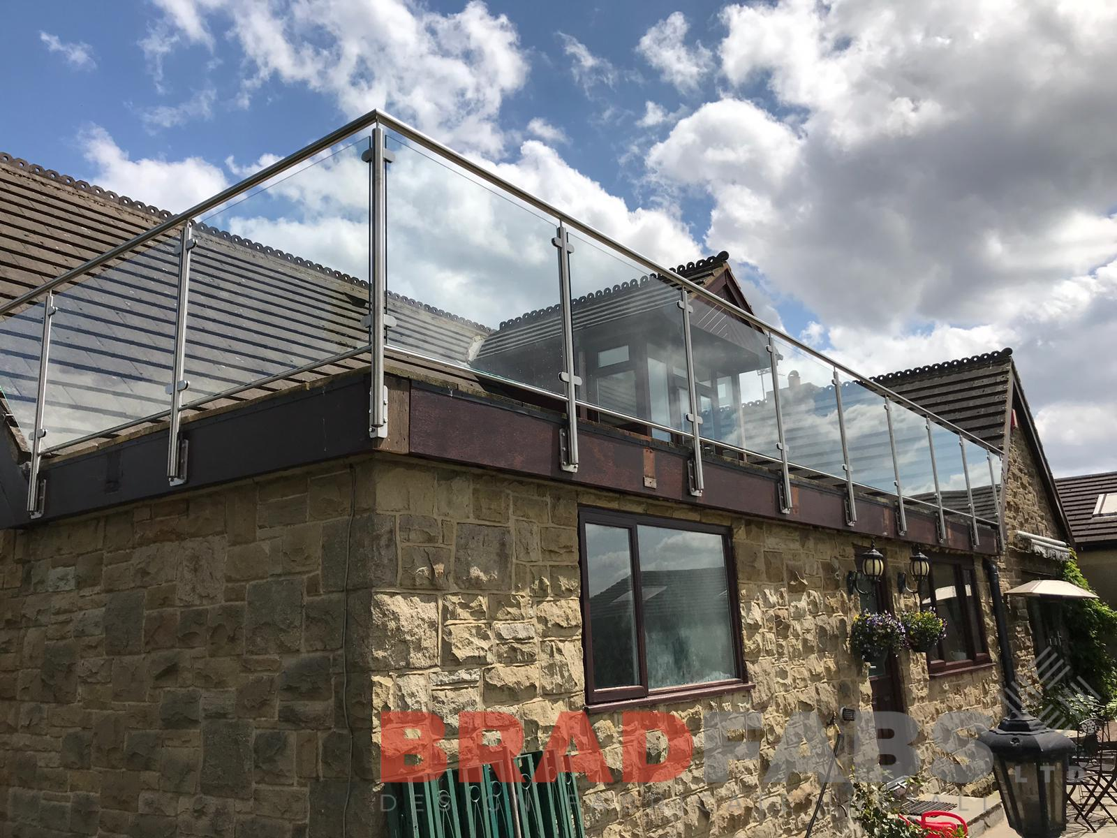 Bespoke balustrade added to customers existing flat roof, 10mm toughened safety glass infill panels with stainless steel toprail by Bradfabs Ltd