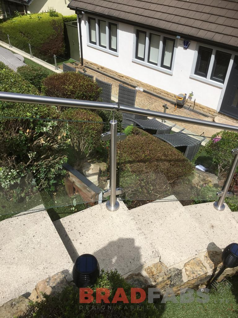 stainless steel post and top rail with glass infill panels for a domestic property by Bradfabs